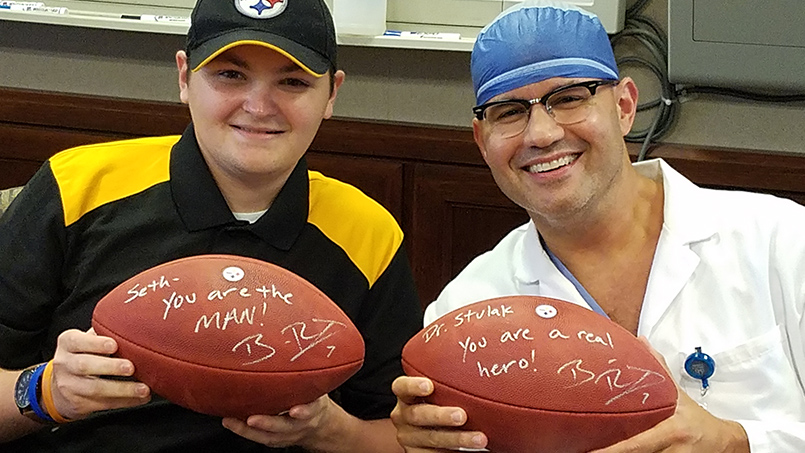 patient Seth Bayles smiling with Dr. John Stulak, each holding autographed footballs from Pittsburgh Steelers quarterback Ben Roethlisberger