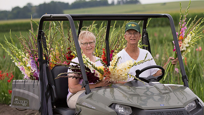John and Barb Meyer in their farm jeep and surrounded by blooming gladiolas