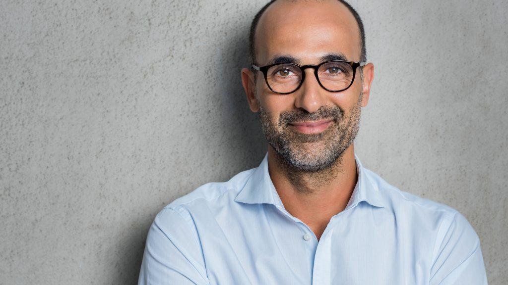 Retrato de un hombre maduro y con lentes sobre un fondo gris