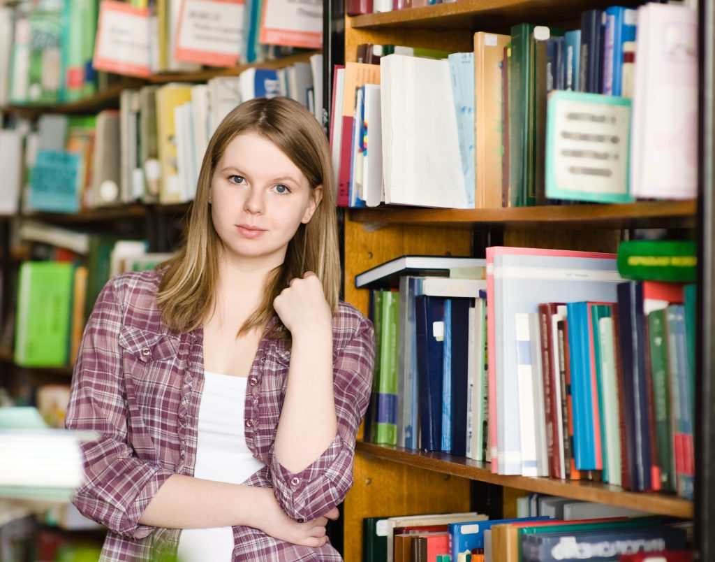a serious or pensive-looking teenage girl in a library