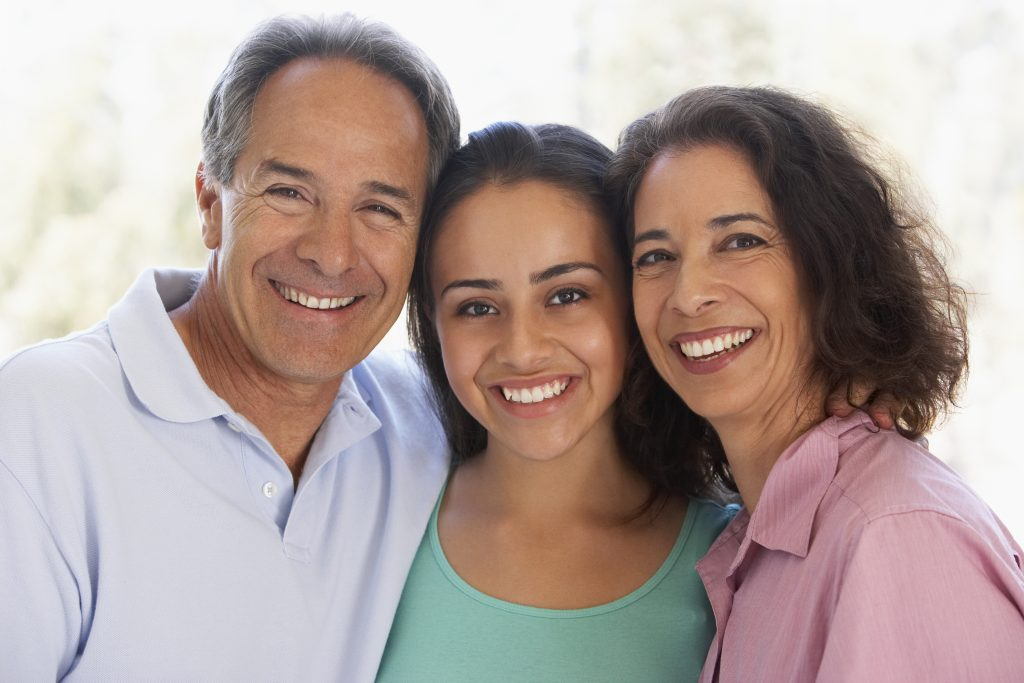 a close-up of a middle-aged couple and their daughter, all smiling