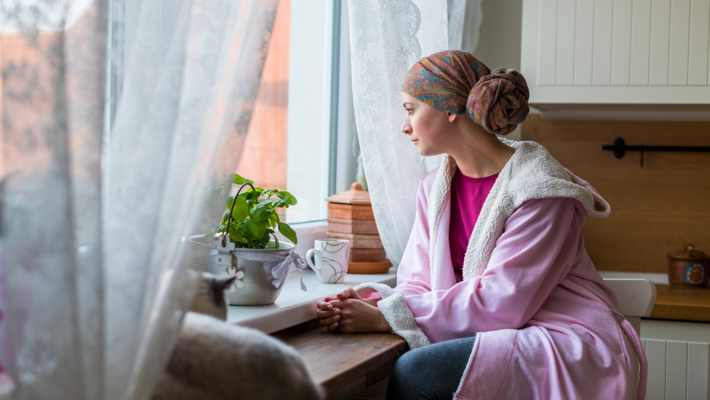 Una mujer joven con cáncer lleva un pañuelo en la cabeza y una bata en el cuerpo mientras está sentada en la cocina y mira por la ventana