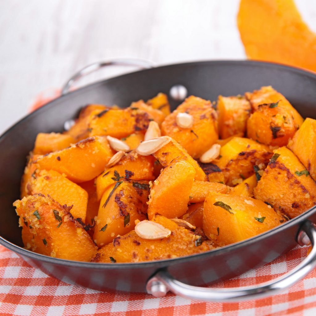 a cooking pan filled with healthy, nutritional cubed squash or pumpkin with seasoning