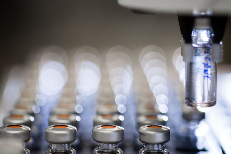 research laboratory microscope and medicine vials