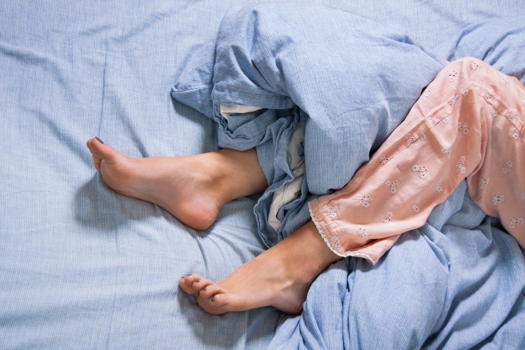 a close-up of a woman's lower legs and feet in a bed, sticking out of and tangled in the sheet and blanket