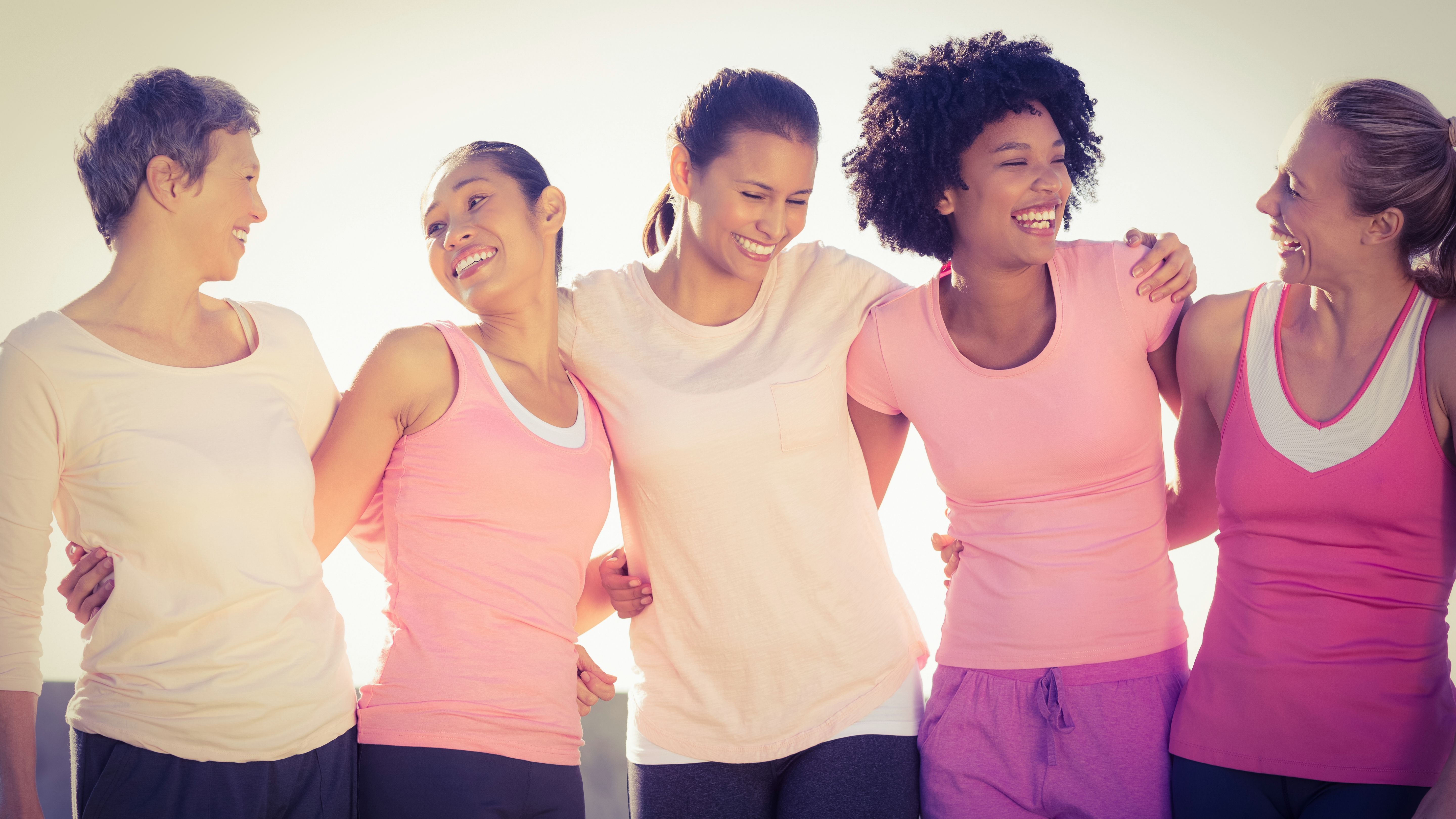 a group of multi ethnic women, all wearing pink to support breast cancer awareness, linking arms and smiling