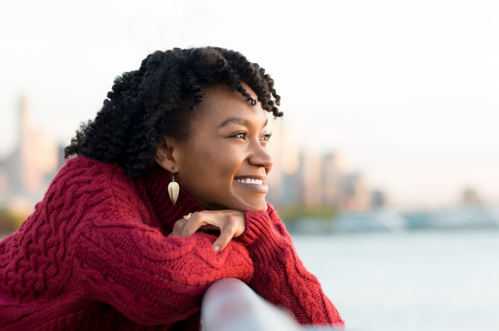 a young African American woman smiling and happy, leaning on a bannister overlooking the water and looking into the sunshine with confidence