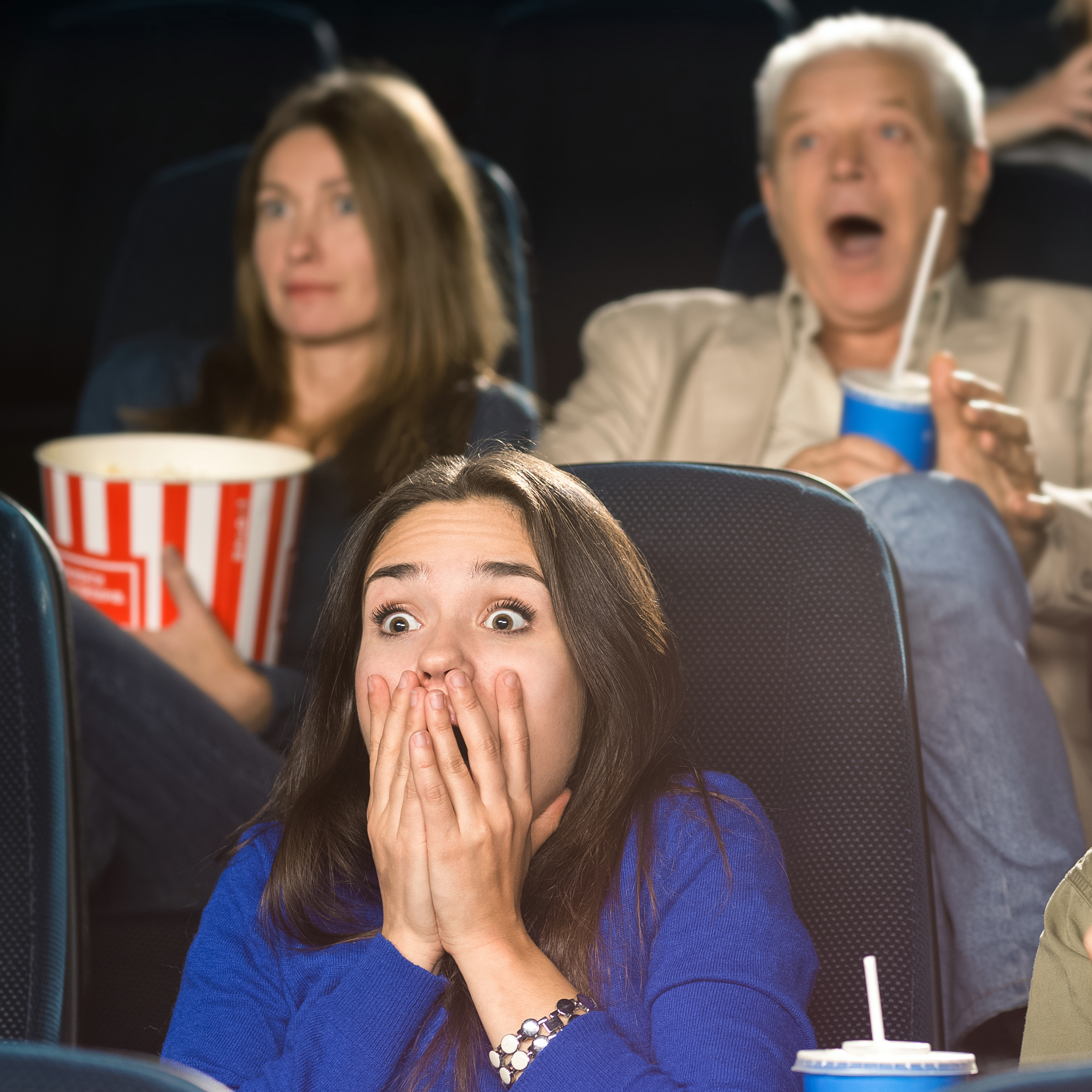 a movie theater with people in their seats holding popcorn and looking frightened and scared