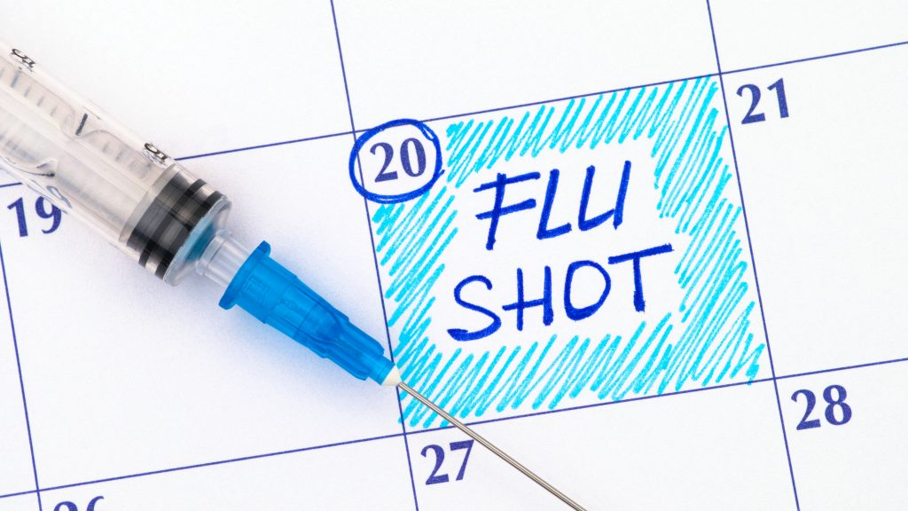 a calendar of dates with a needle on the paper and a flu shot reminder written on the page