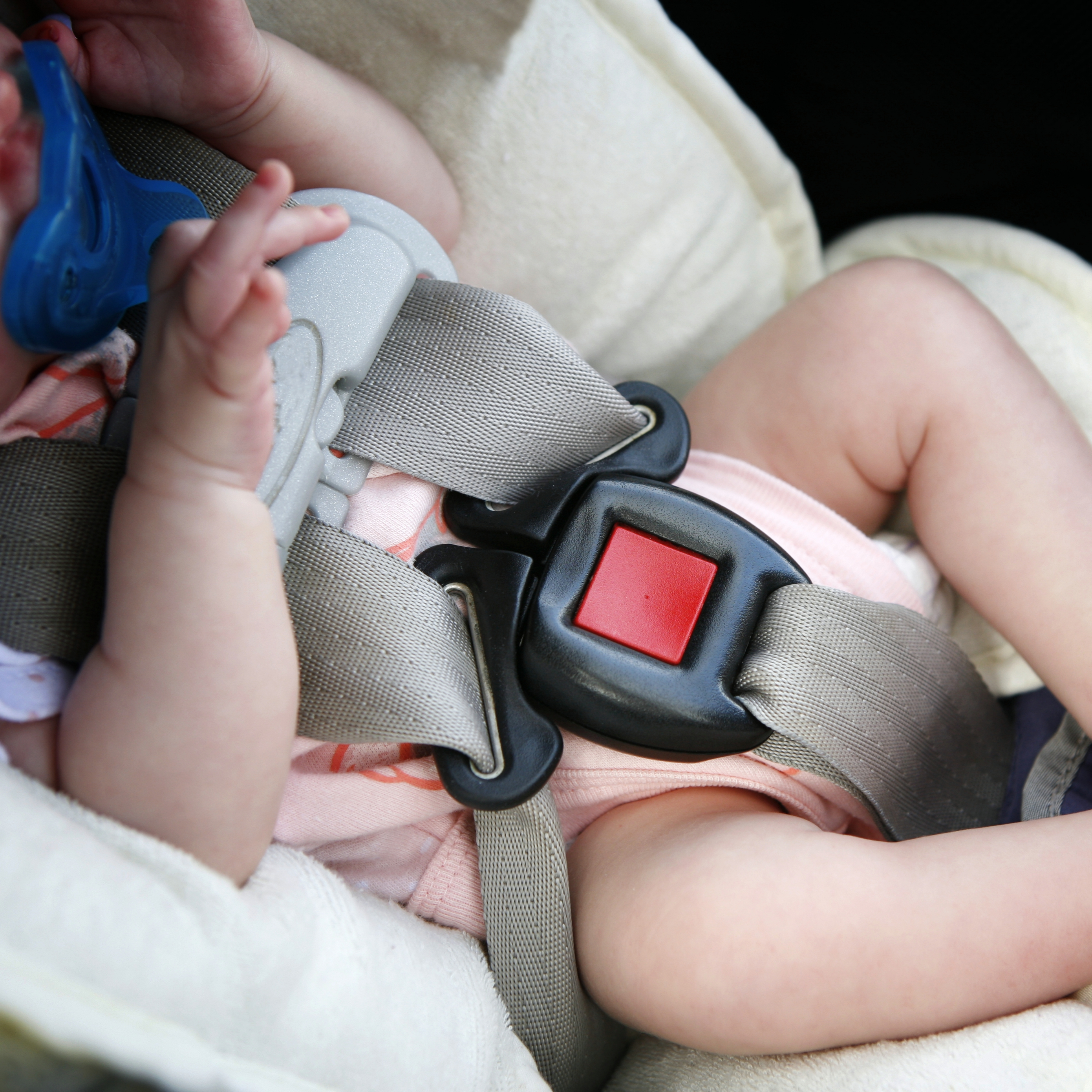 a baby buckled in a car seat for safety