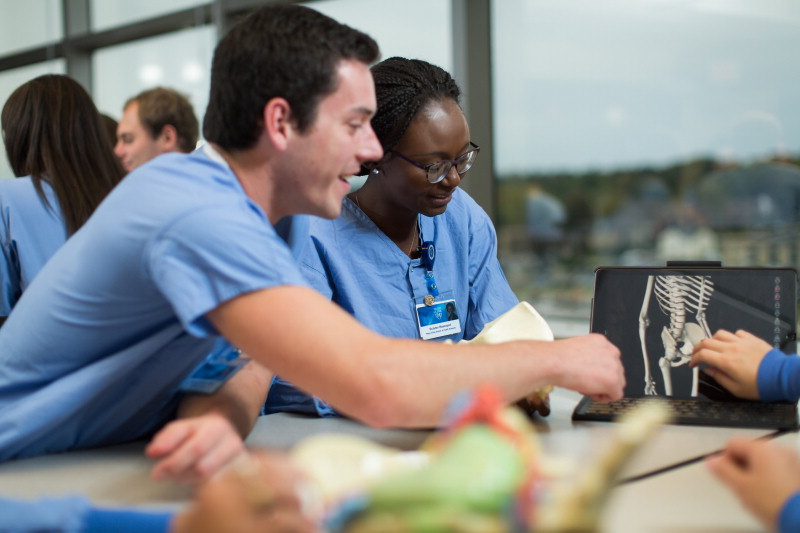 students dressed in blue scrubs viewing skeleton on laptop