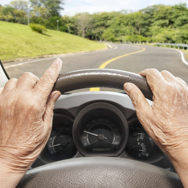 Elderly person driving a car slowly on a highway