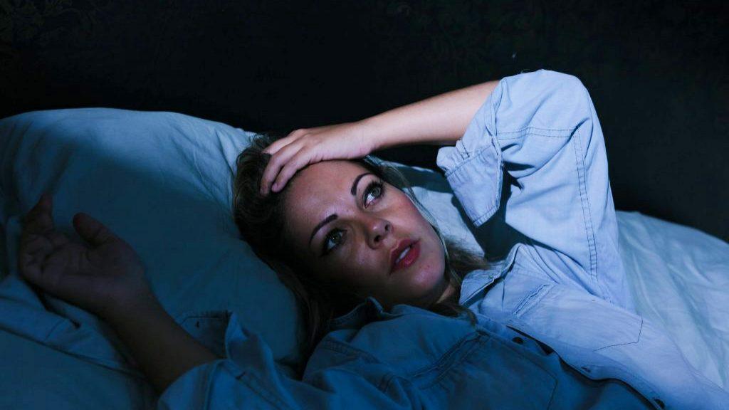 Una mujer joven está acostada en una habitación oscura, con los ojos bien abiertos y la mano en la frente, sin poder dormir porque sufre de insomnio o estrés
