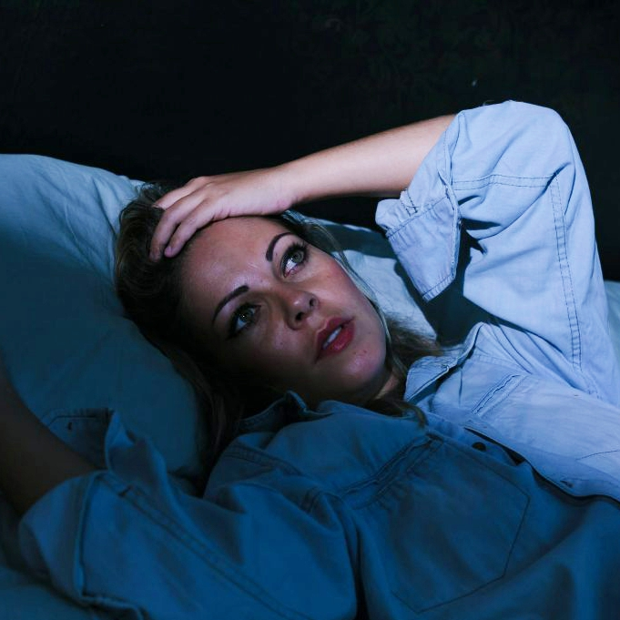 a young woman in bed in a dark room, lying awake with her eyes open and her hand on her forehead, not sleeping and suffering from insomnia or stress