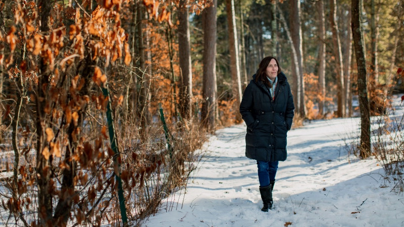 multiple myeloma patient Stacy Erholtz walking on a snow-covered path in the woods