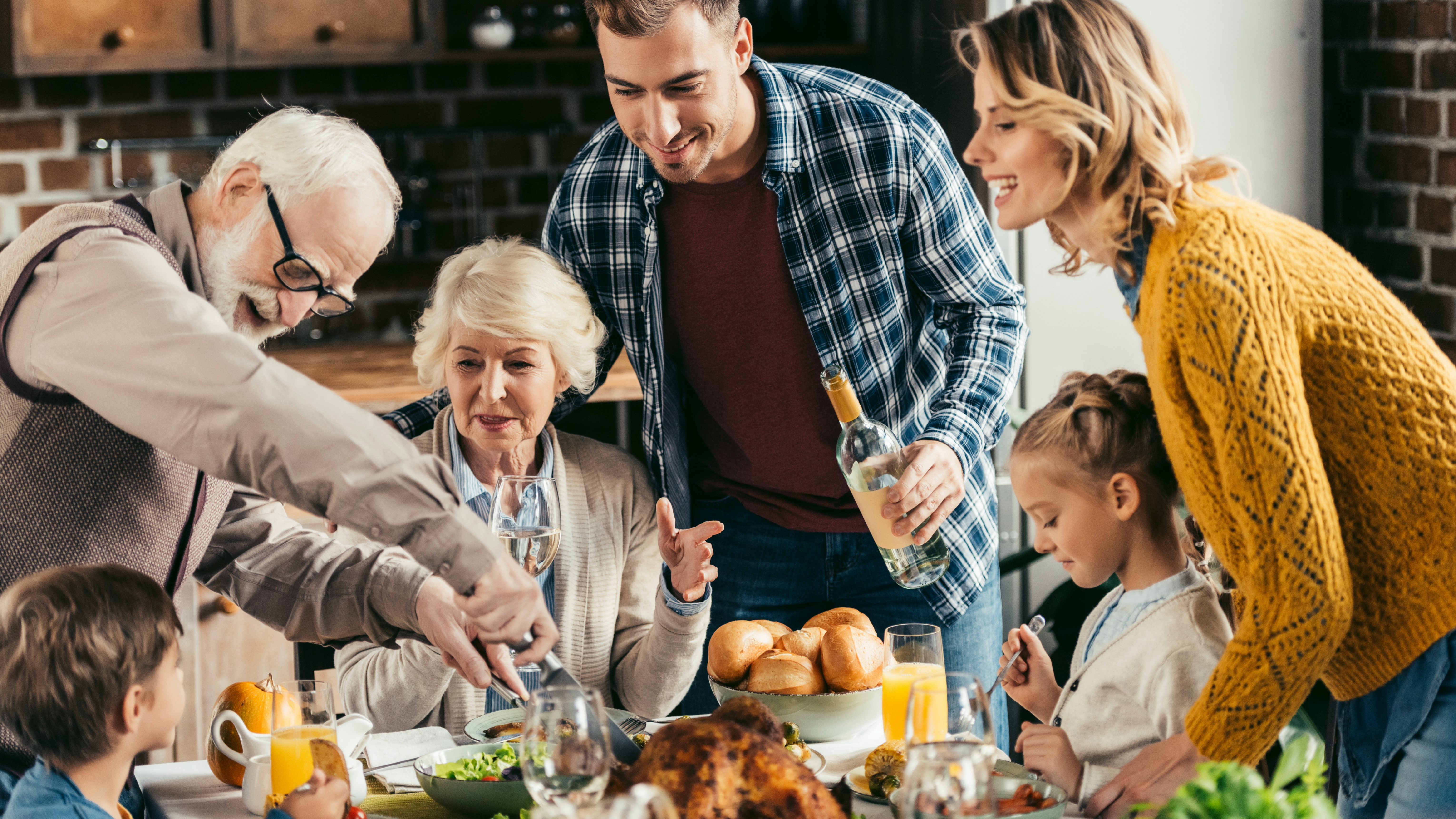a multi-generational family with grandparents and children gathered at the dinner table for a turkey dinner at the holidays