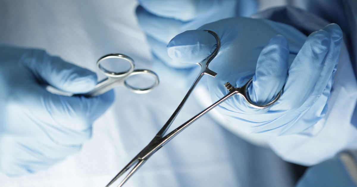 closeup of a surgeon's hands with gloves, holding surgical instruments