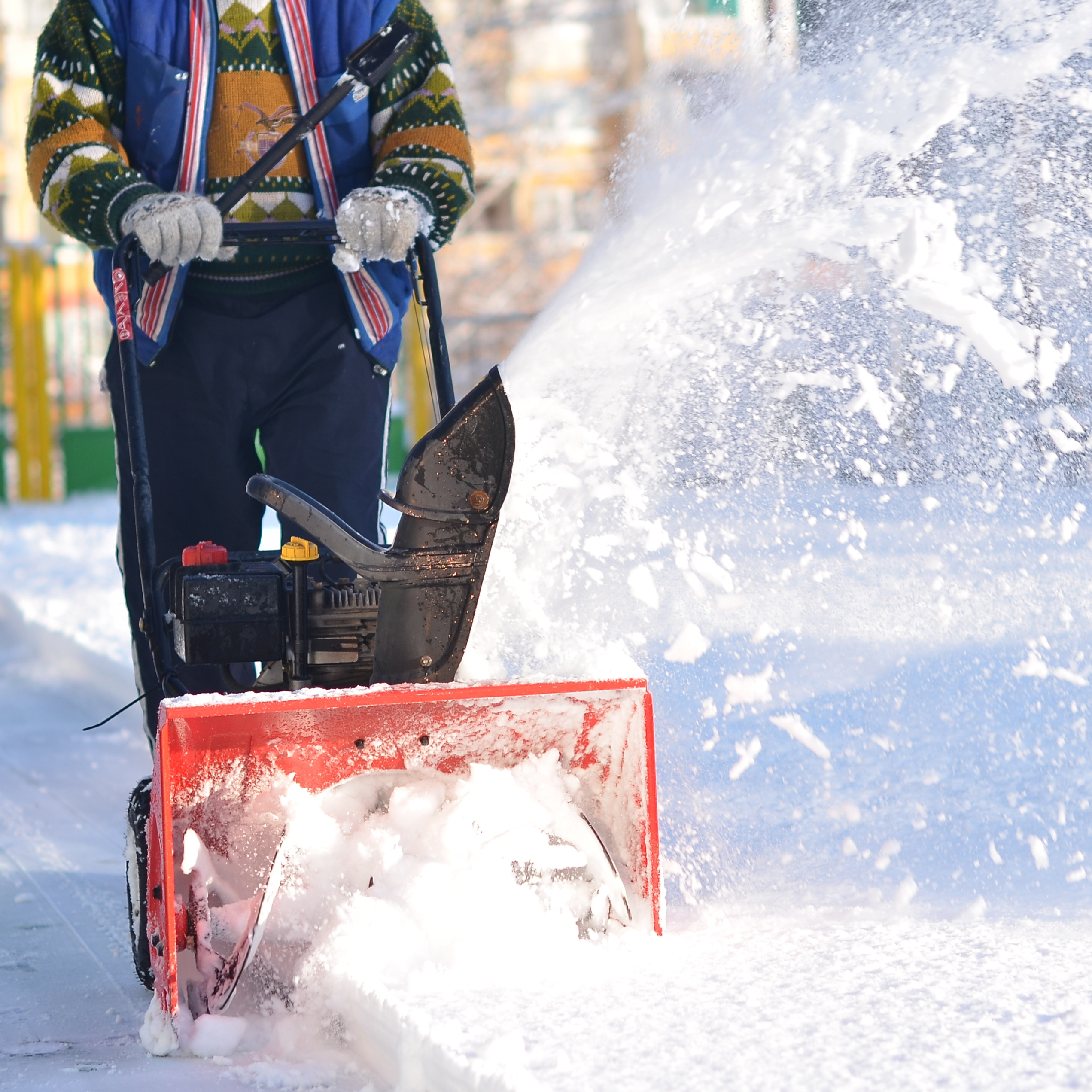 A man pushing a snowblower down a sidewalk.