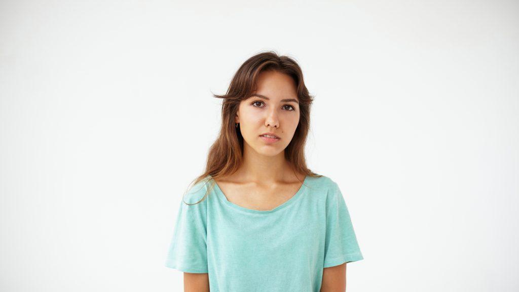Retrato de una adolescente con ropa demasiado grande que mira a la cámara y pone una expresión seria o pensativa en la cara