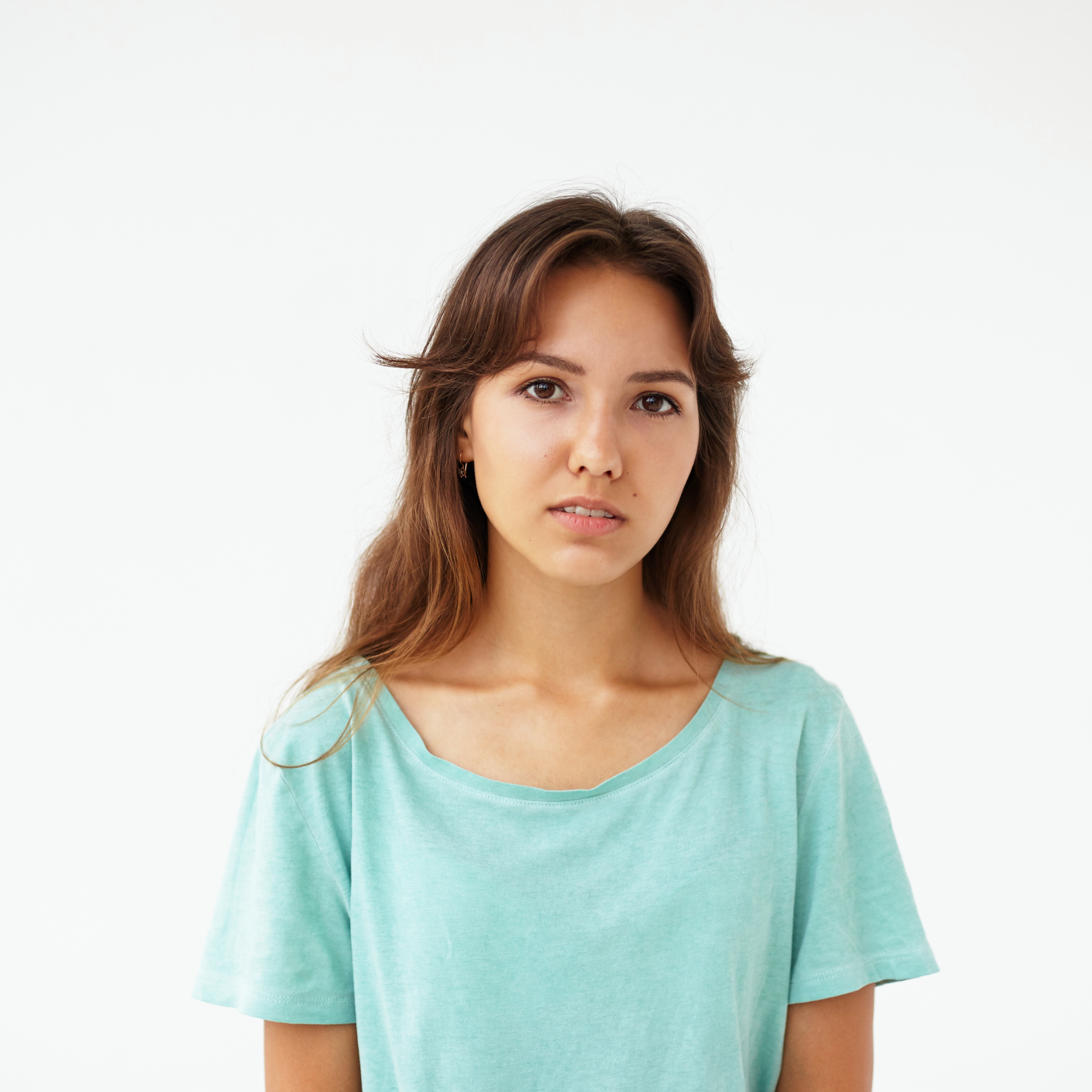 Portrait of teenage girl wearing oversize top looking at camera with serious or pensive expression on her face.