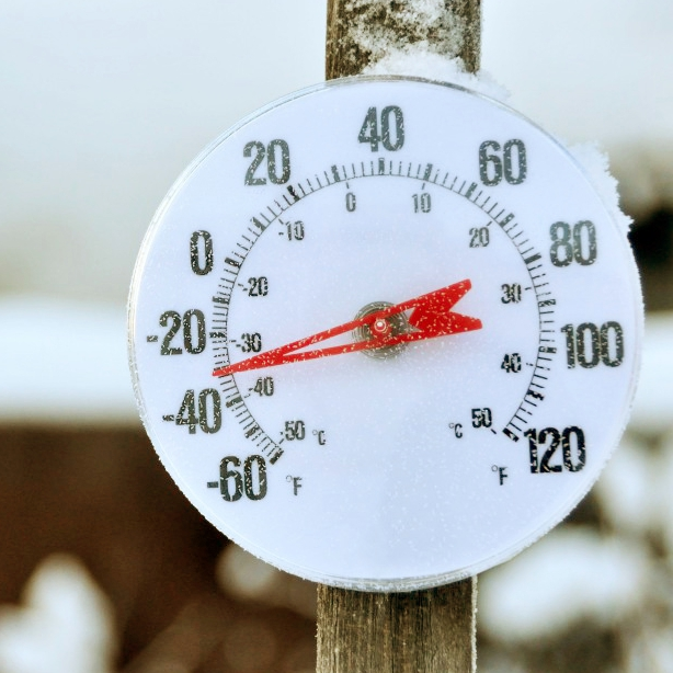 an outdoor thermometer measuring outside freezing temperatures