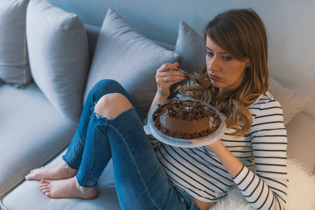 a young woman sitting on a couch eating an entire cake, looking sad or depressed - emotional eating