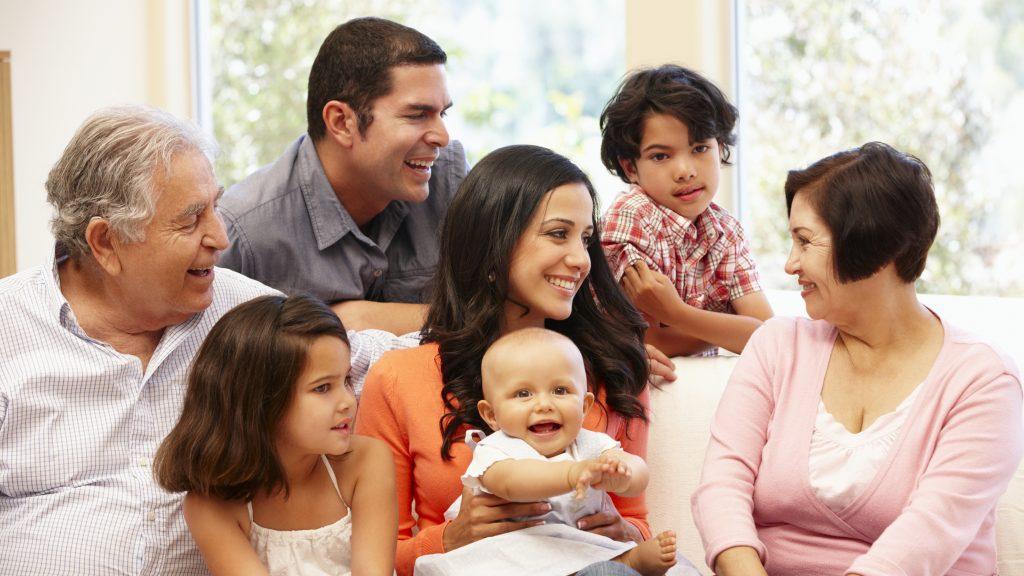 Una familia feliz y sonriente de varias generaciones sentada en un sofá en una sala de estar