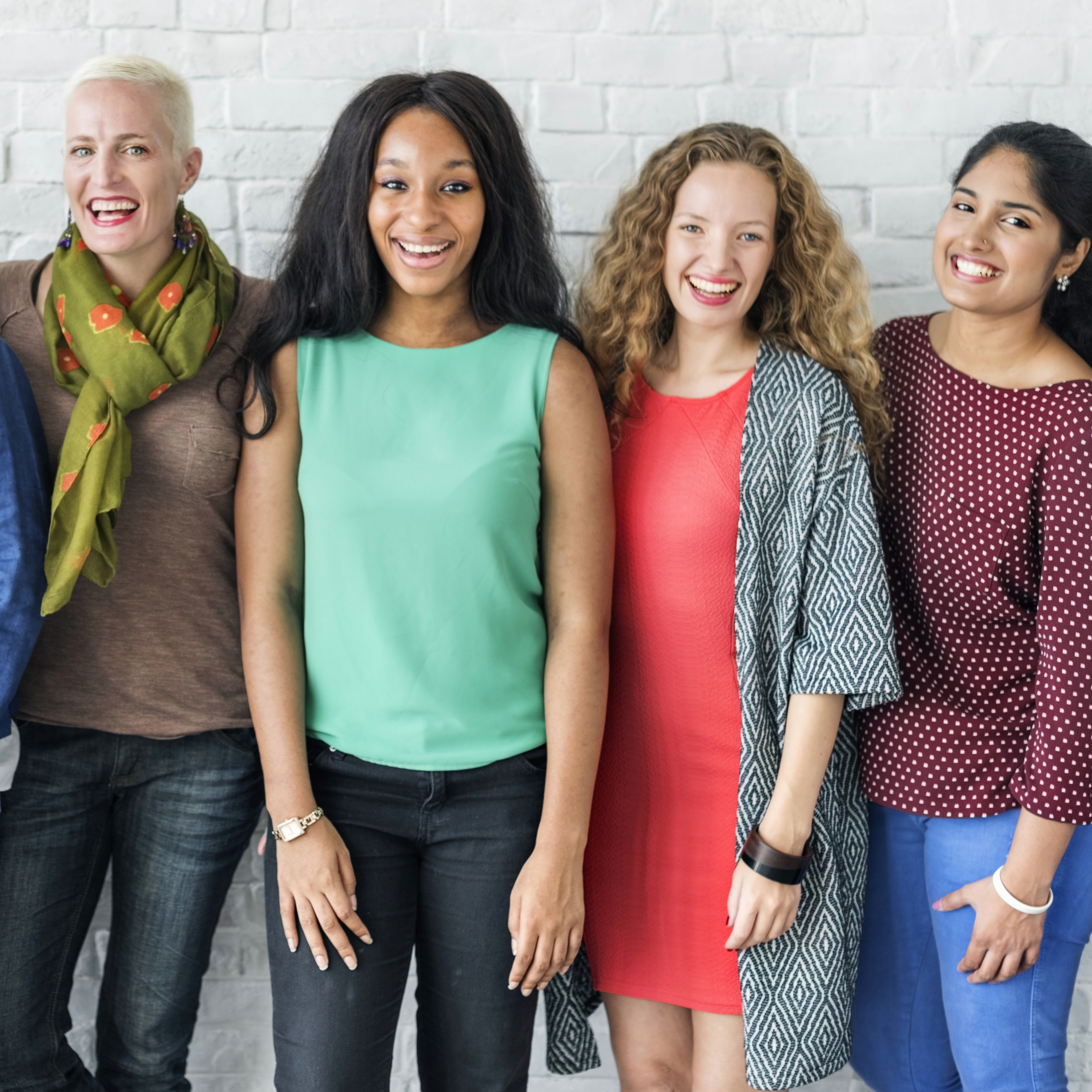 a diverse group of happy, smiling women standing near a brick wall for a background