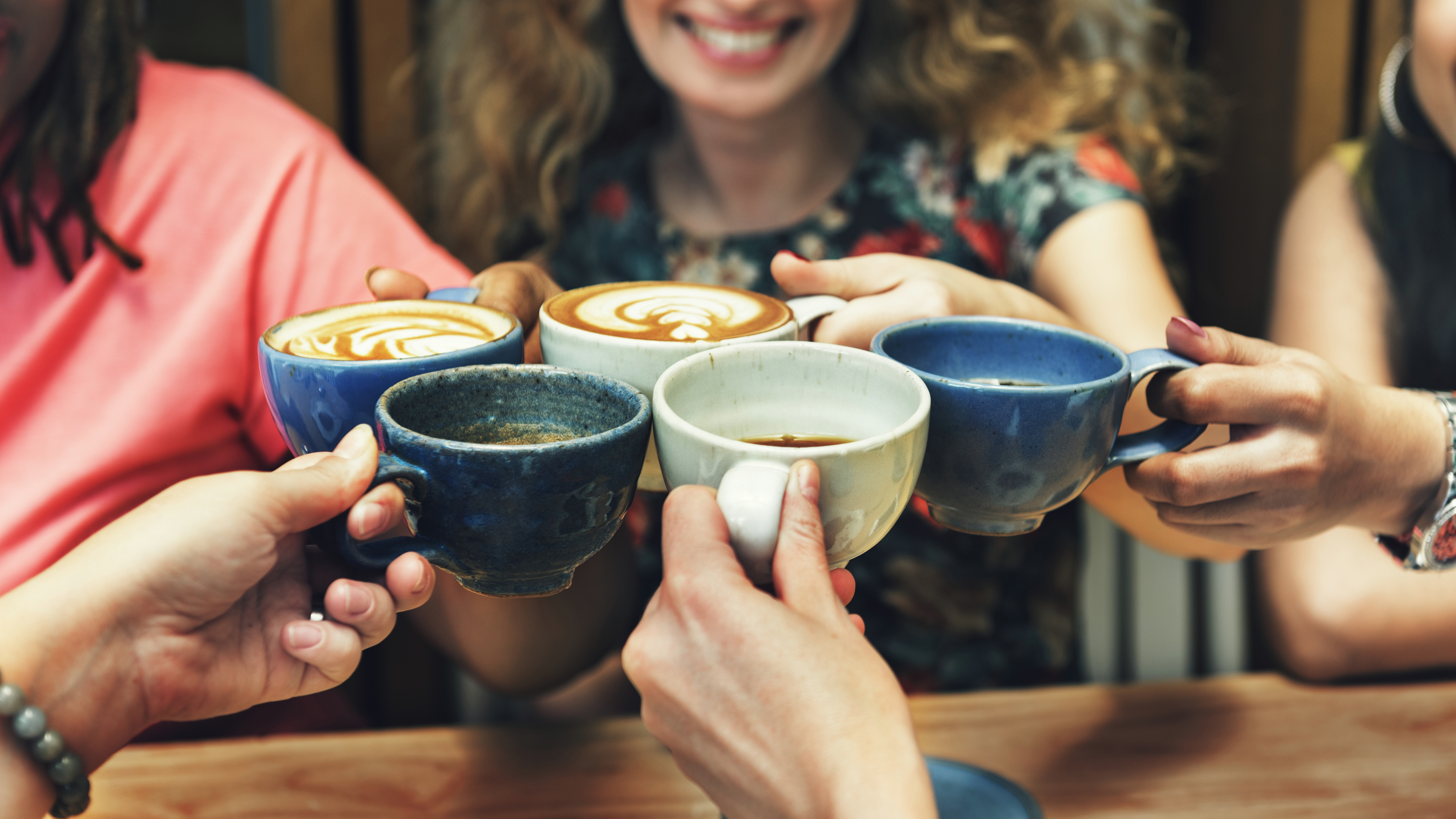 a group of happy diverse women, smiling and sharing cups of coffee together