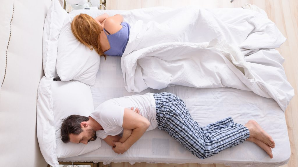 a middle-aged couple in bed with their backs to each other, sleeping or maybe upset, angry, frustrated