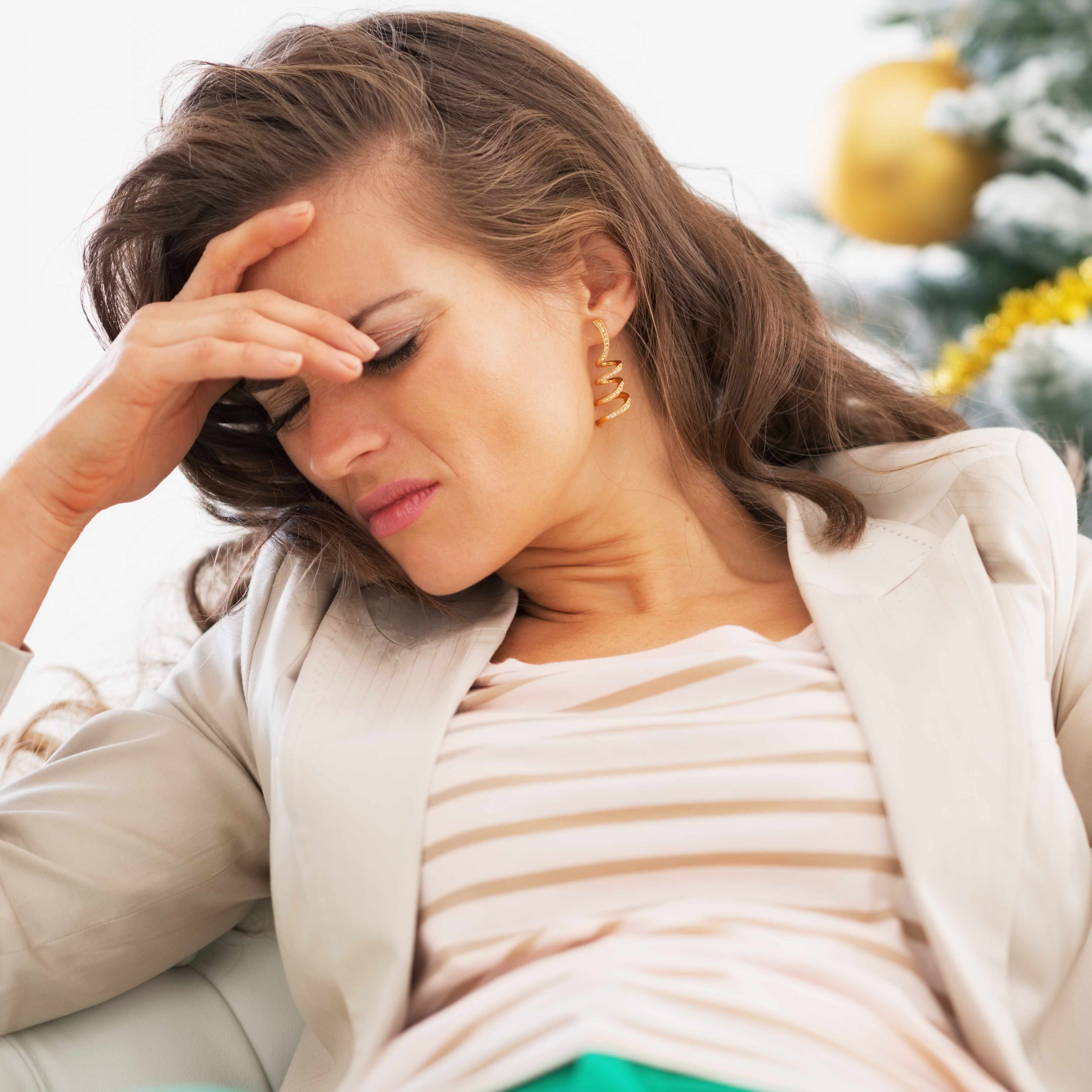 A woman stressed out in front of a holiday Christmas tree.