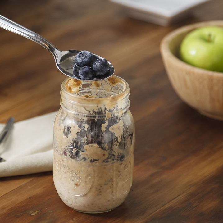 a person putting a spoonful of blueberries into a clear mason jar with refrigerator oatmeal