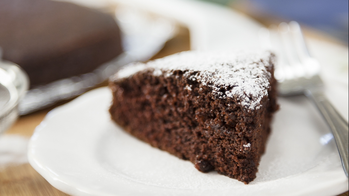 a slice of soft chocolate cake with powdered sugar sitting on a plate