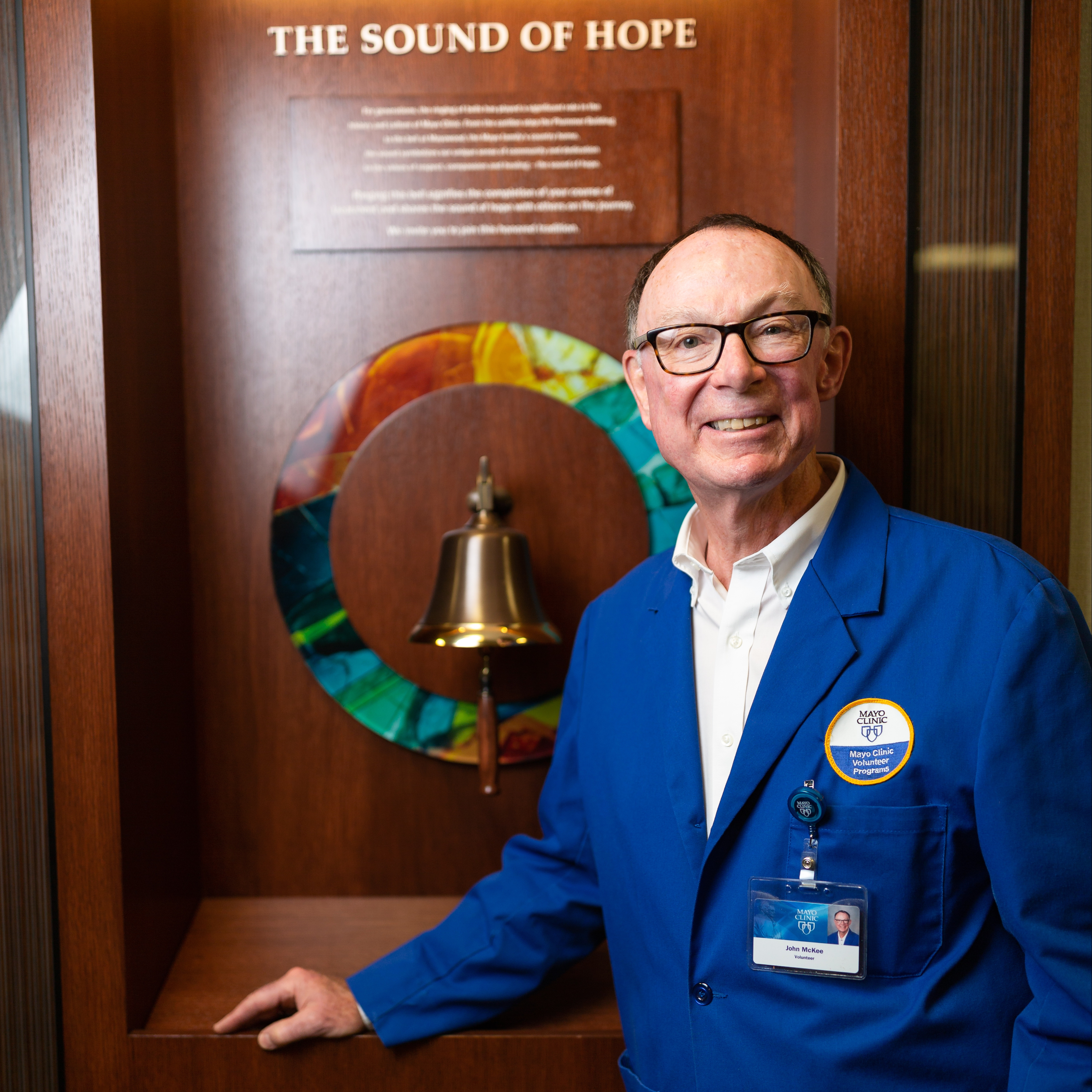 volunteer and cancer patient John McKee standing by the Sound of Hope bell