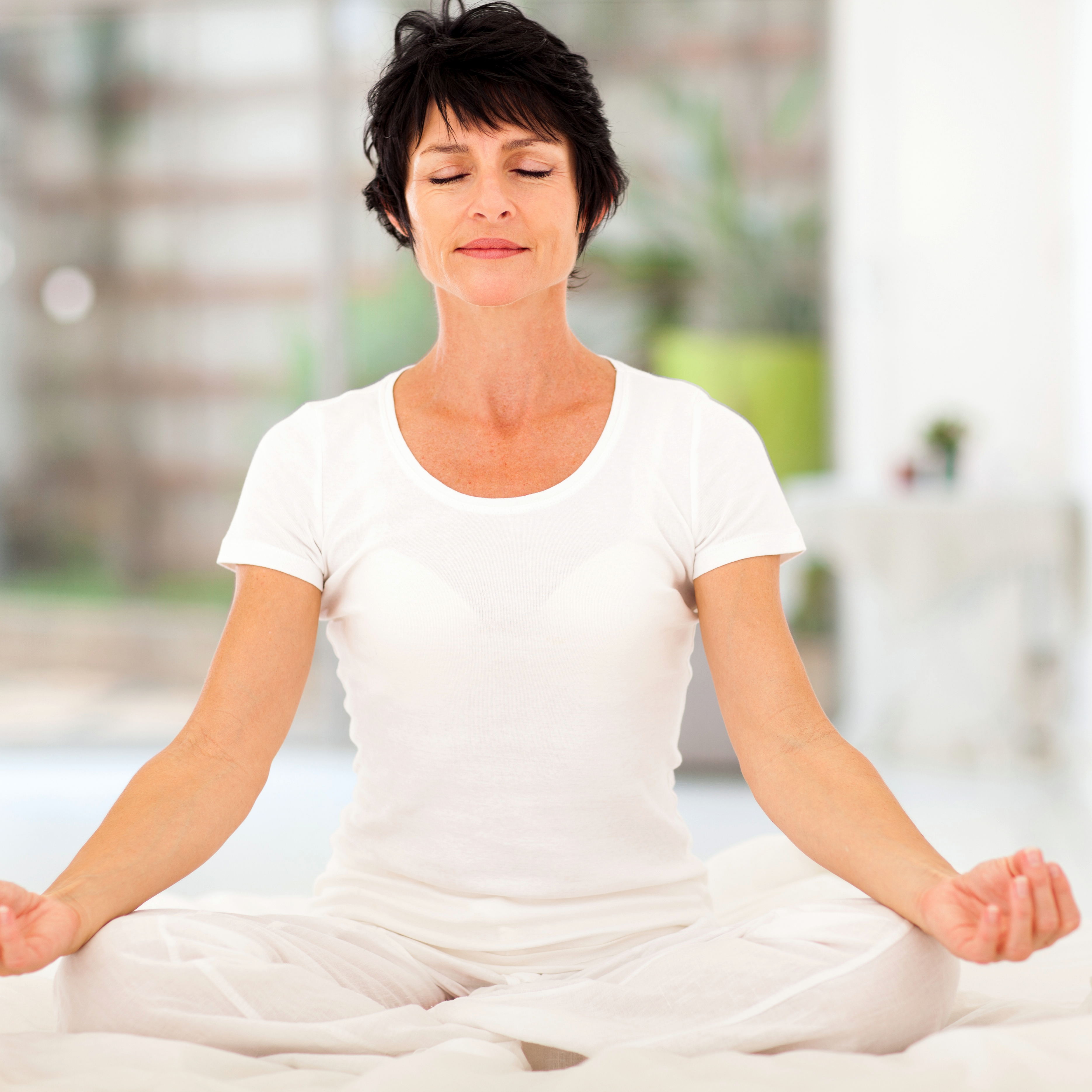 Middle-aged woman meditating on bed at home