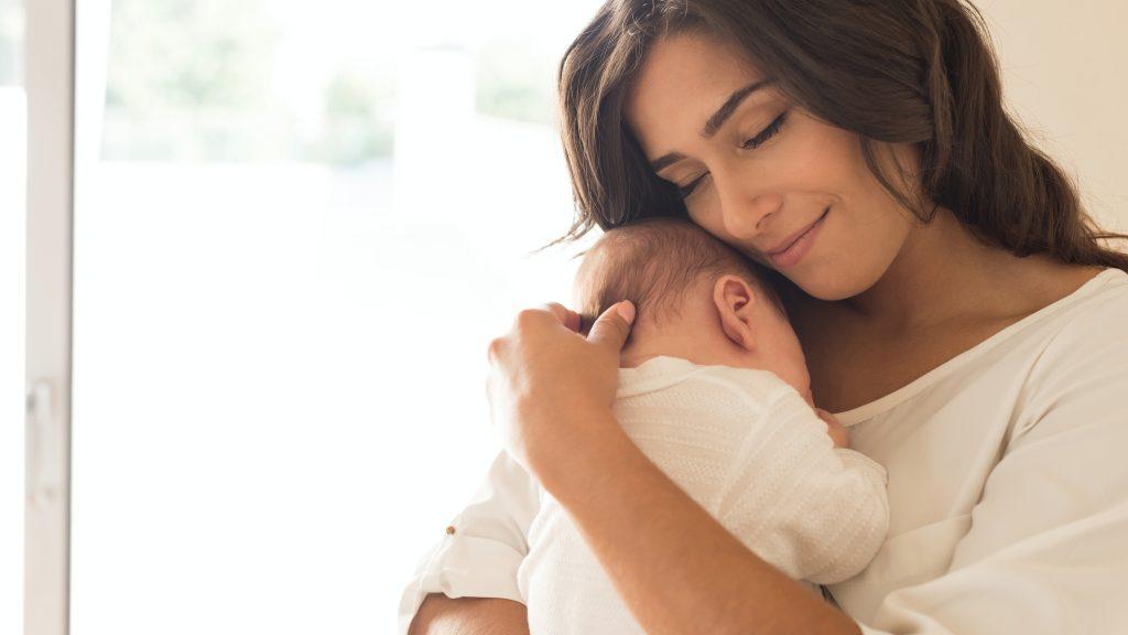 Una mujer joven sostiene en brazos a un recién nacido