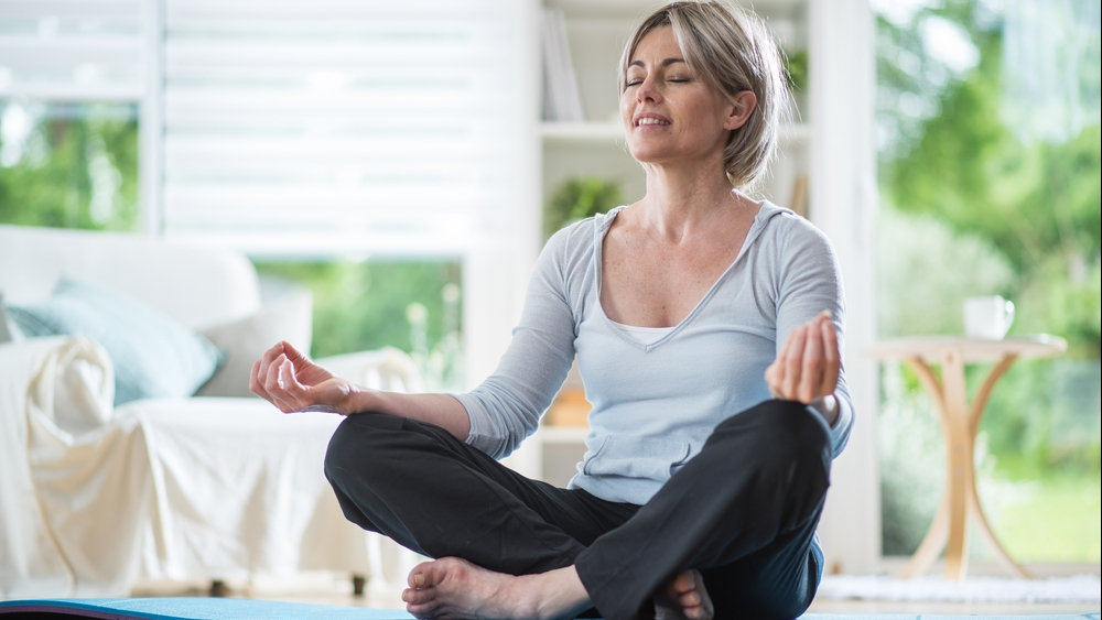 middle-aged woman sitting in the lotus position and meditating