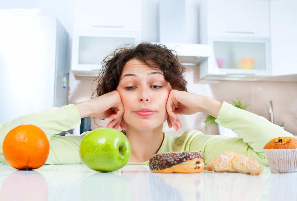 a woman in a kitchen looking at healthy fruit and sugary donuts and pastries, trying to decide which to eat