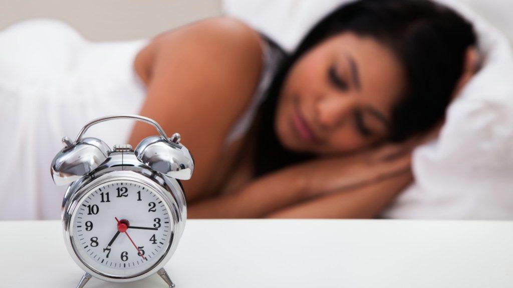 Reloj despertador en la mesita de noche de una mujer dormida