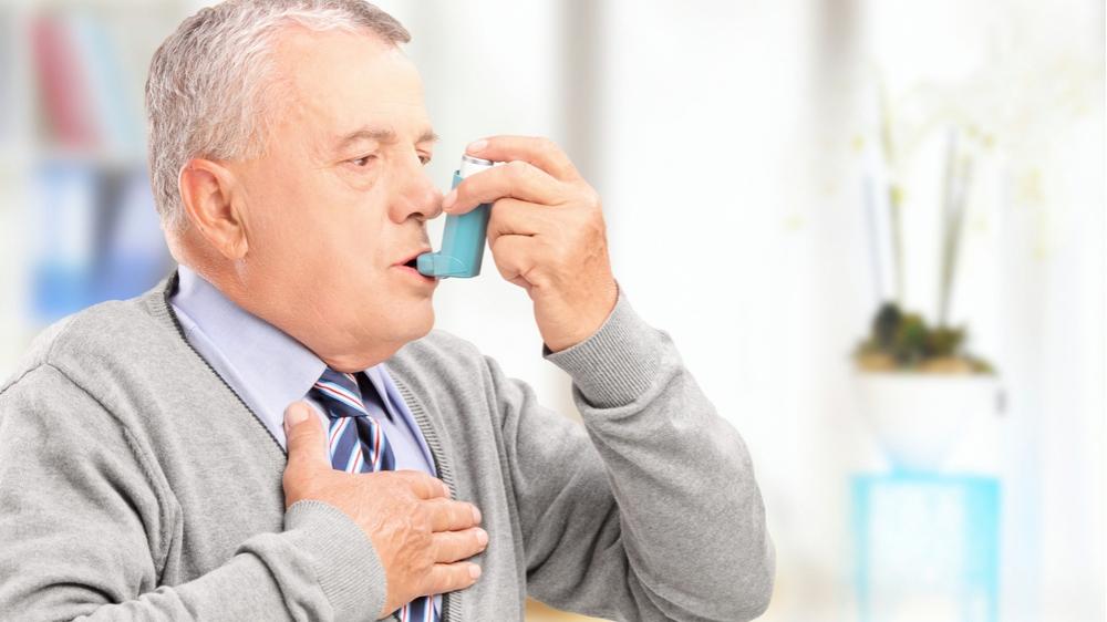 Un hombre maduro usa un inhalador en casa
