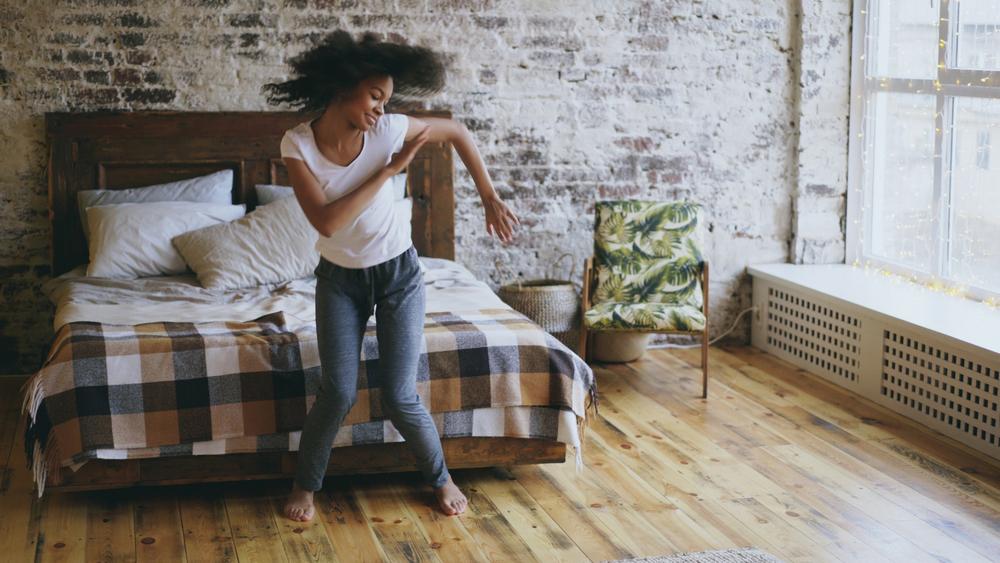 a happy, joyful young woman dancing in her bedroom