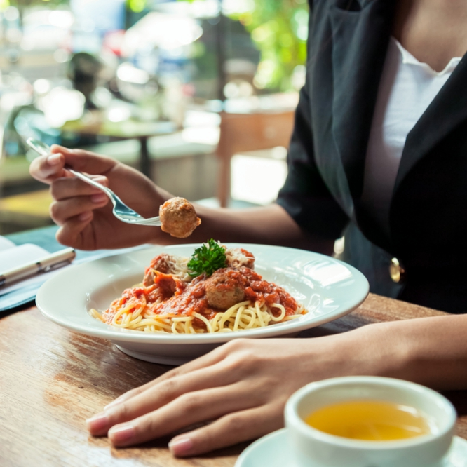 close up of woman eating spaghetti meatball with notebook by plate