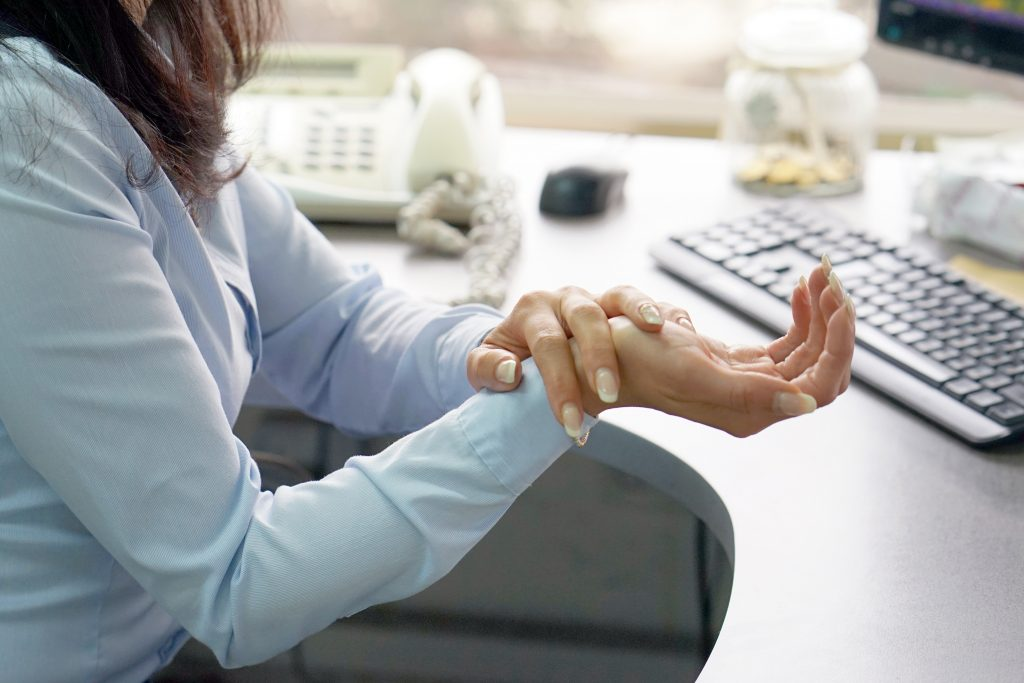 a woman sitting at a computer holding her wrist because of pain and injury