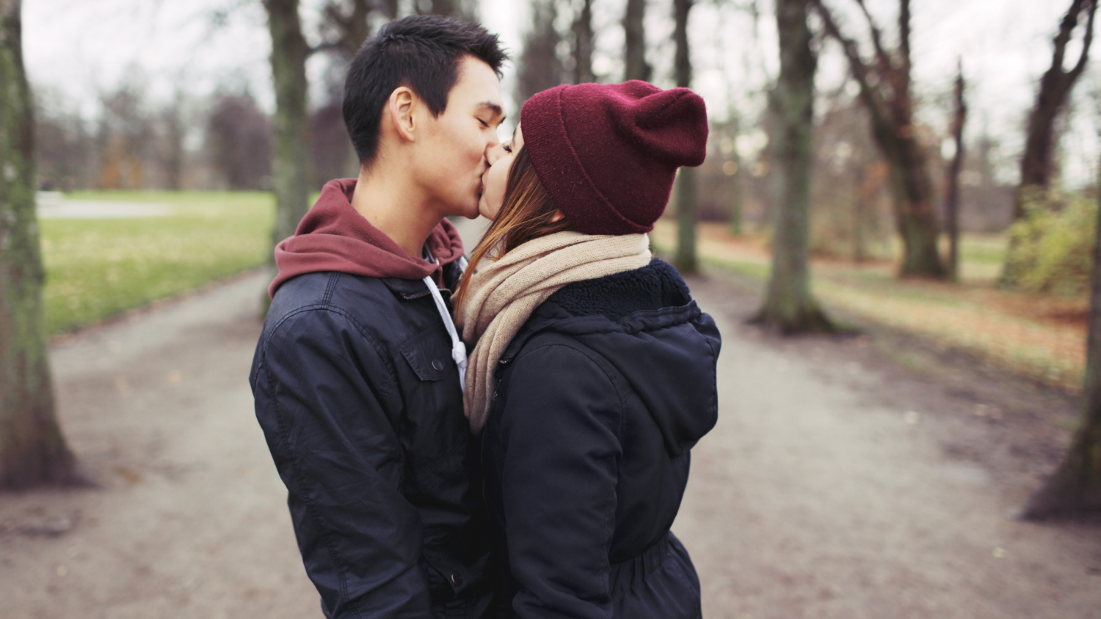 a young man and woman standing outside in a park, kissing