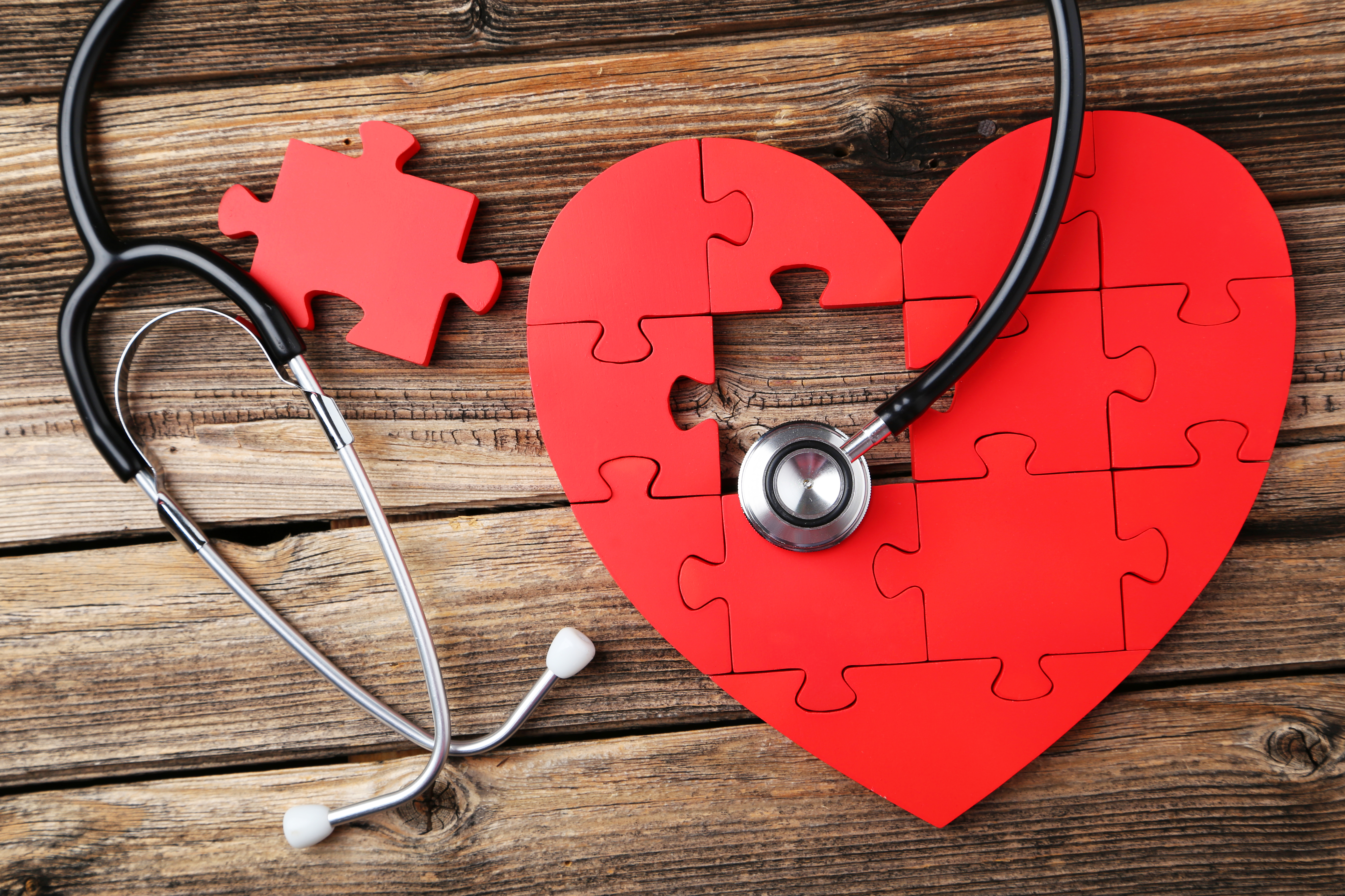 a red heart-shaped puzzle and a stethoscope on a rough wooden surface