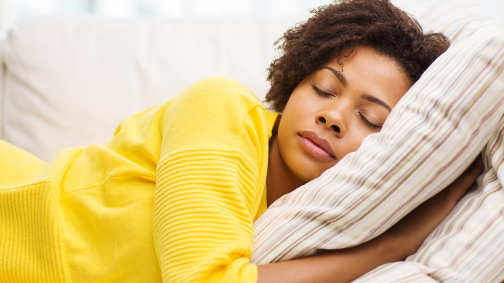 a young African American woman sleeping on a sofa with a pillow