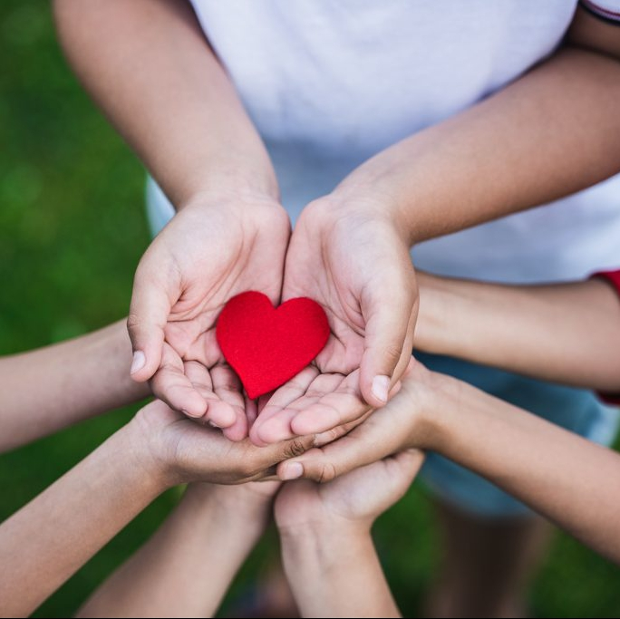 a group of children in a circle with their hands together holding a red paper heart.