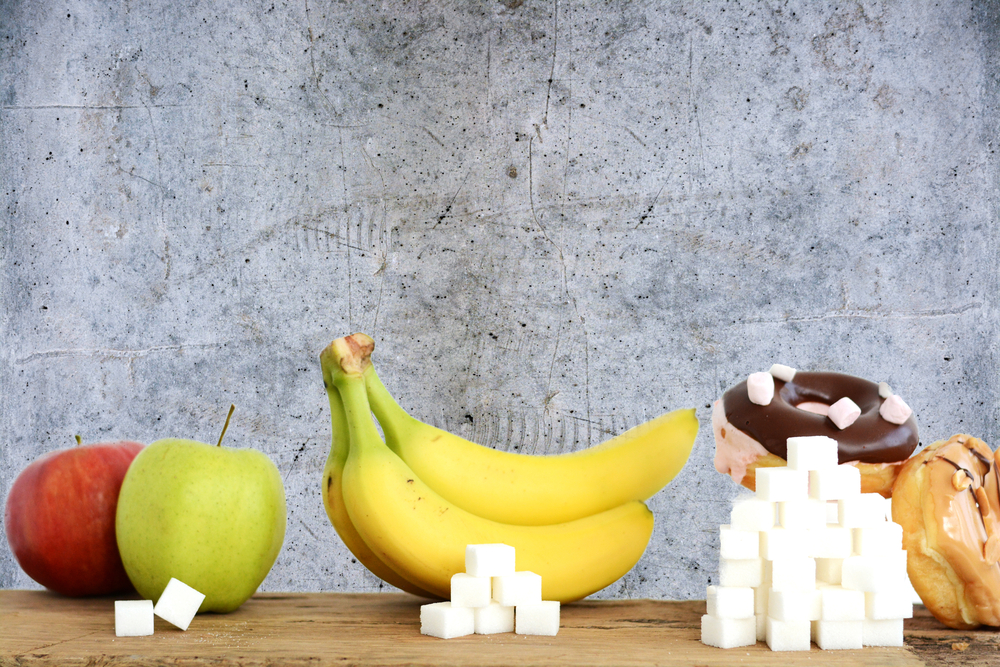 three foods - apples, bananas and pastries - with piles of sugar cubes in front of each, illustrating relative sugar content of each