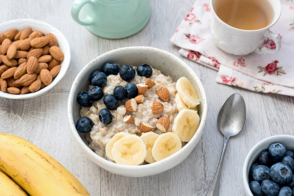 a healthy vegetarian breakfast of oatmeal porridge with banana, blueberries and nuts and cup of green tea