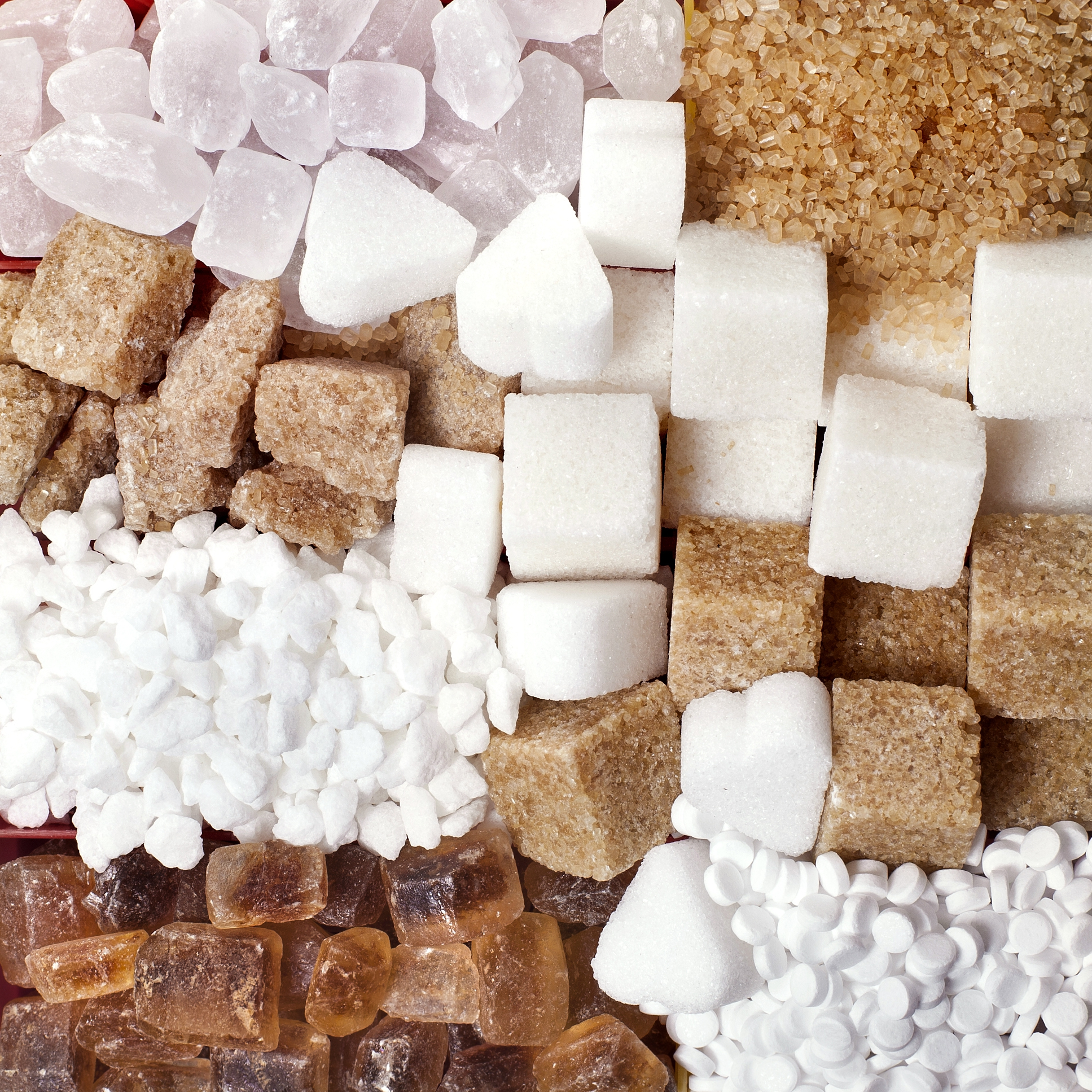 Closeup of sugar cubes and crystals with sweeteners